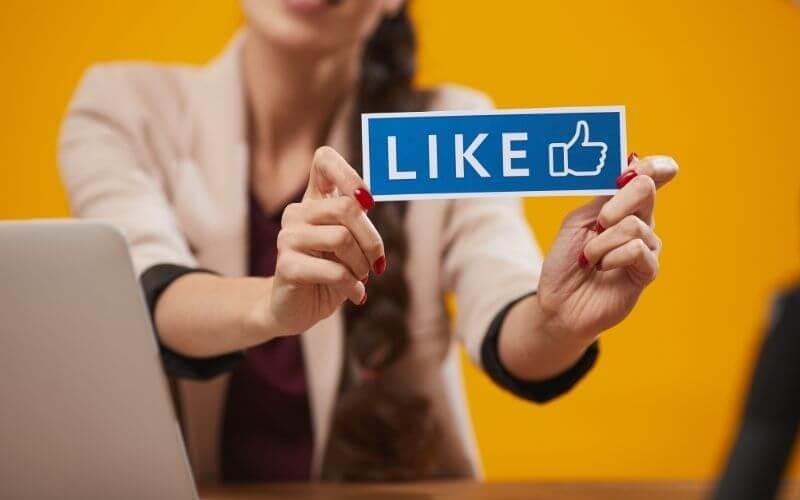 """Kobieta trzymająca tablicę """"like""""."""
